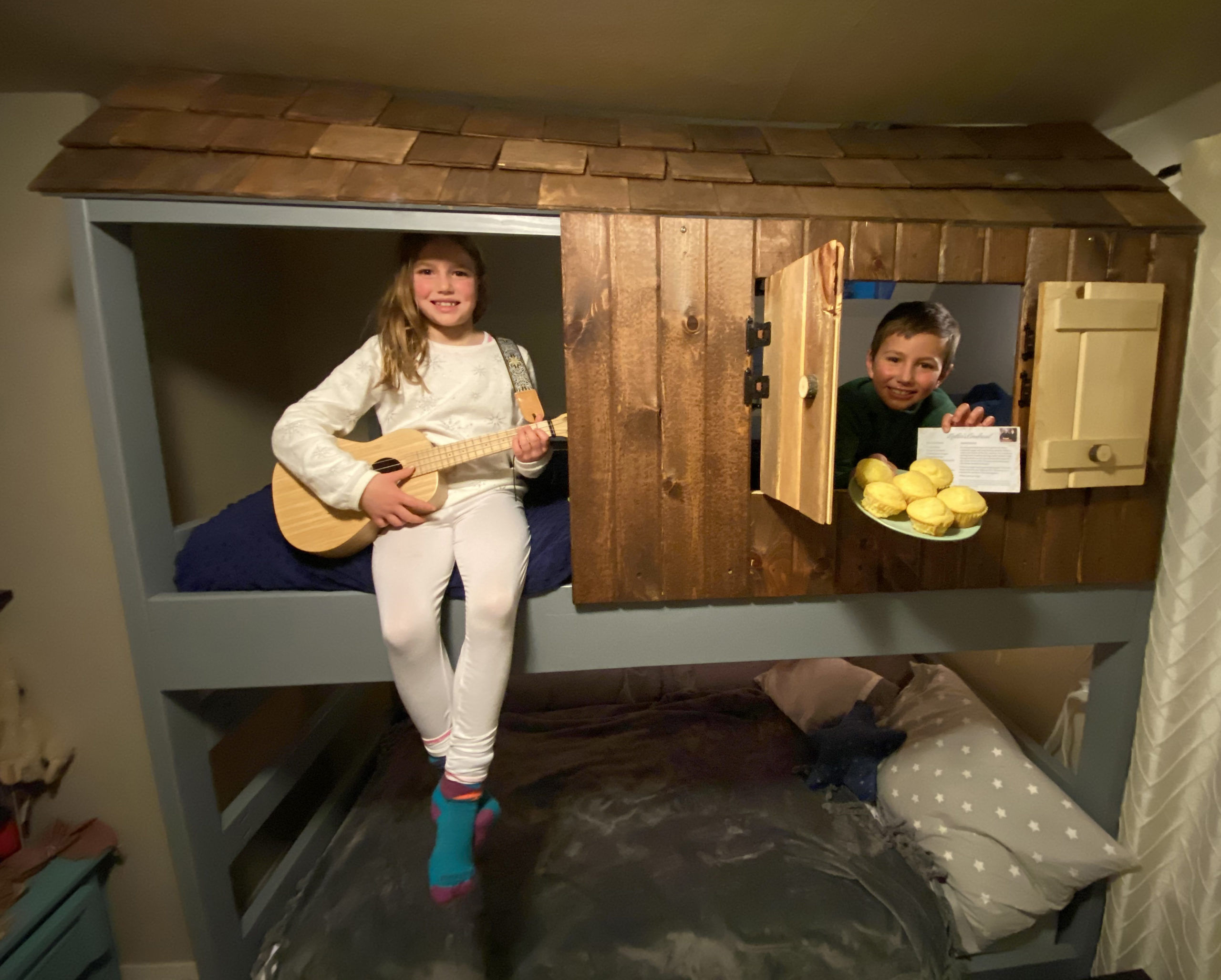 Elijah and Oona sit in their bunkbed with cornbread.